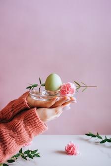 Hände, die moderne art ostereier mit rosa farbe malen