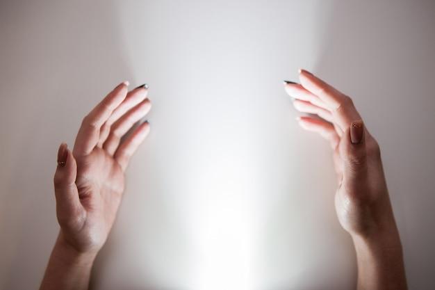 Hände, die nach heiligem licht greifen. wunderglaube an gott und religionskonzept