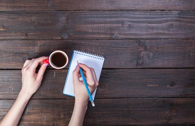 Hände, die notizbuch und kaffeetasse halten.