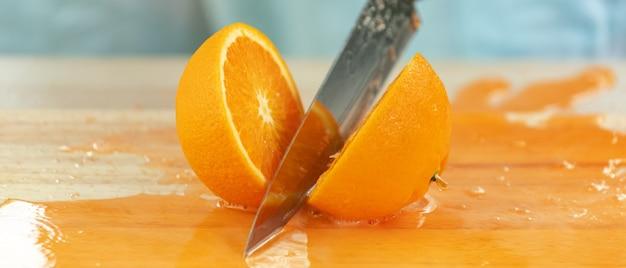 Hände, die orange mit einem spritzer orangensaft auf holzschneidebrett schneiden