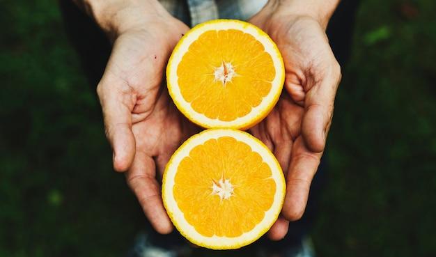 Hände, die orange organisches erzeugnis vom bauernhof halten