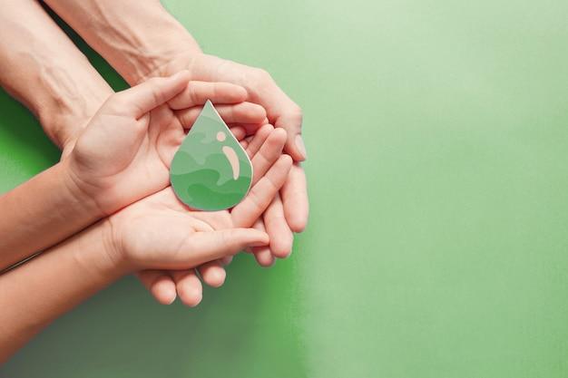 Hände, die papier halten, schneiden grünen öltropfen, csr, erneuerbare grüne energie des biokraftstoffs