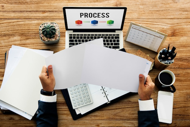 Hände, die papier halten und an grafischer überlagerung des laptopnetzes arbeiten