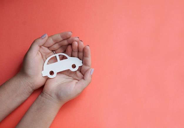 Hände, die papierautoausschnitt halten, auf dem farbhintergrund, familienschutzkonzept