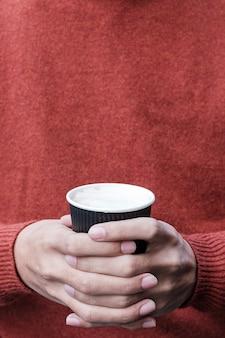 Hände, die pappbecher des heißen kaffees halten. kostenloses plastikbehälterkonzept