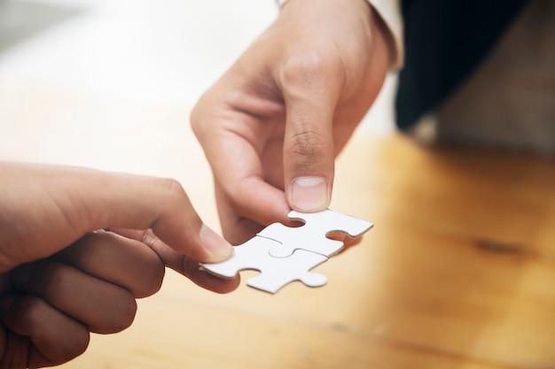 Hände, die puzzlen halten