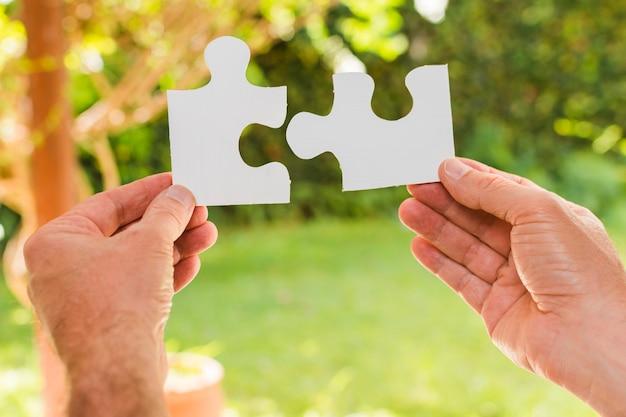 Hände, die puzzleteile halten