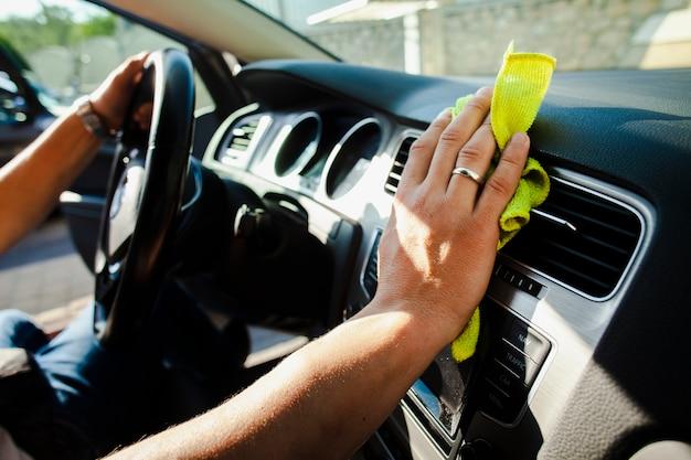 Hände, die rad halten und innenraum des autos polieren