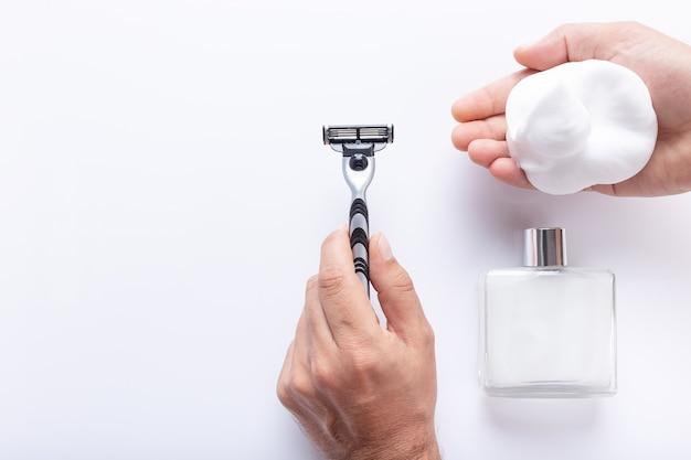 Hände, die rasierklinge und rasierschaum halten, mit nach rasur lokalisiert auf weißem hintergrund, mit kopierraum, draufsicht. rasierprodukte für männer.