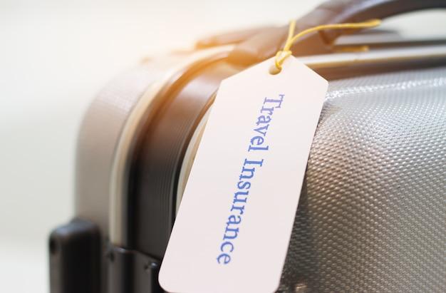 Hände, die reiseversicherungstag auf koffersicherheit halten