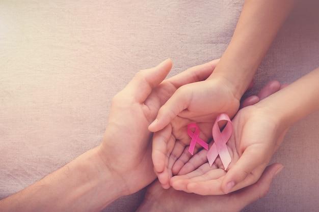 Hände, die rosa bänder, brustkrebsbewusstsein halten