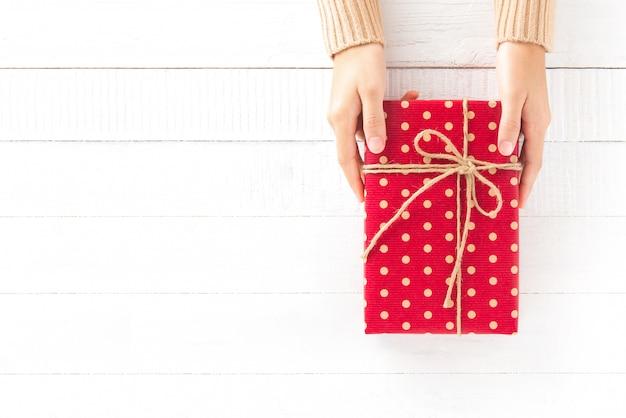 Hände, die rote geschenkbox auf weißem hölzernem hintergrund mit kopienraum geben
