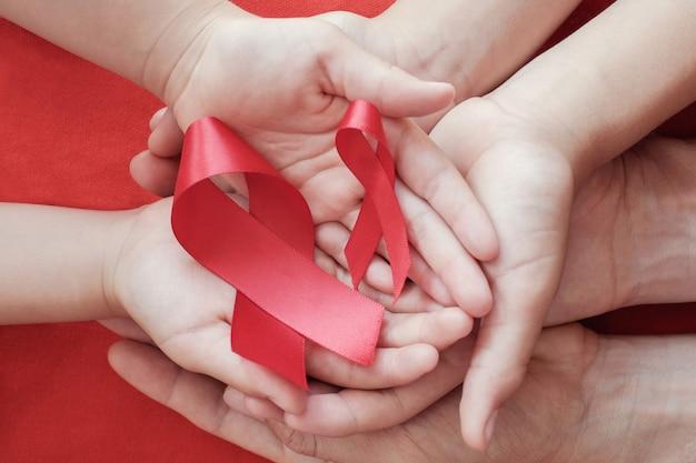Hände, die rotes band auf rotem hintergrund, hiv-bewusstseinskonzept halten