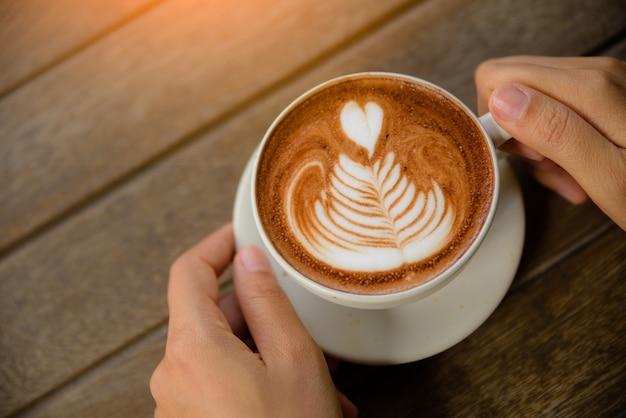 Hände, die schale heißen kaffee latte cappuccino mit dem herzen geformt halten. liebe, hochzeit, valenti