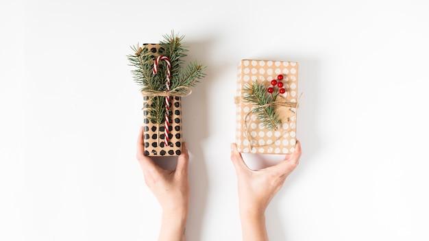 Hände, die schön eingewickelte geschenkboxen halten