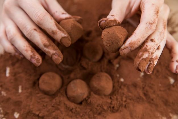 Hände, die schokoladentrüffel mit kakaopulver machen