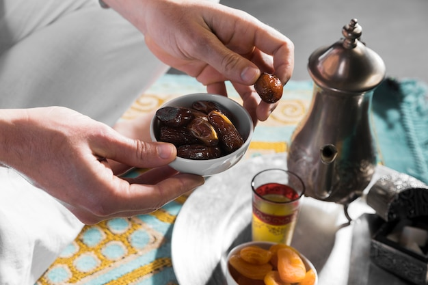 Hände, die schüssel mit arabischen trockenfrüchten halten