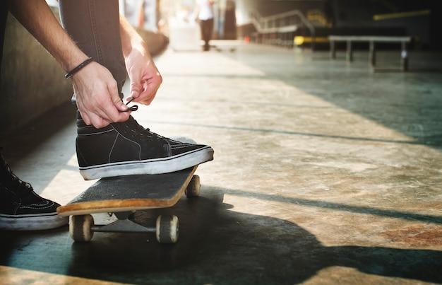 Hände, die schuhroben auf skateboard binden