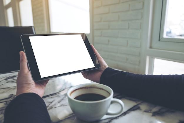 Hände, die schwarzen tabletten-pc mit leerem weißem schirm und kaffeetasse auf tabelle im café halten