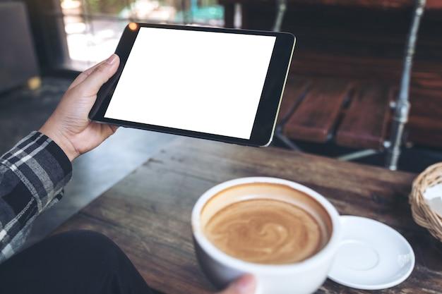 Hände, die schwarzen tabletten-pc mit weißem leerem bildschirm beim trinken des kaffees halten