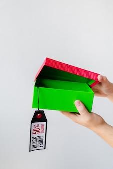 Hände, die schwarzes freitag-geschenk mit tag öffnen