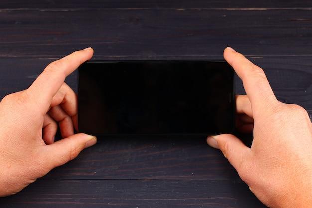Hände, die smartphone auf dunkler holzoberfläche halten