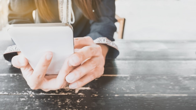 Hände, die smartphone im café halten.