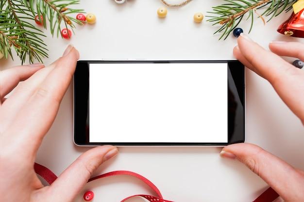 Hände, die smartphone mit leerem bildschirm im rahmen der weihnachts-trumpery halten,
