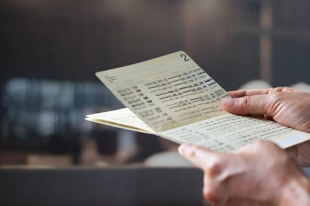 Hände, die sparbuchsparbuch, buchbank auf einem bankbürohintergrund halten