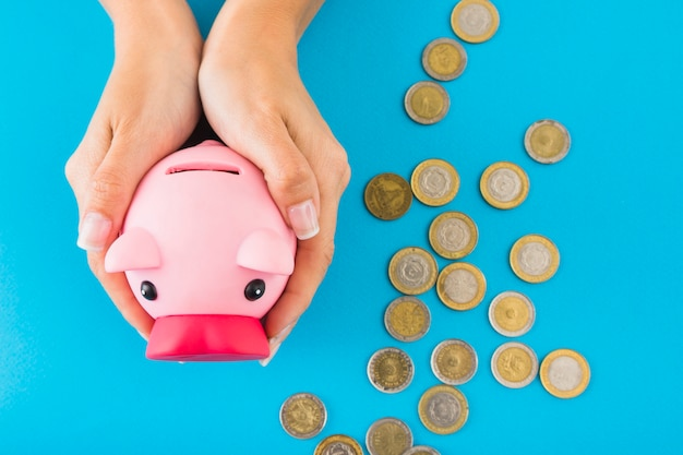 Hände, die sparschwein auf tabelle mit münzen halten