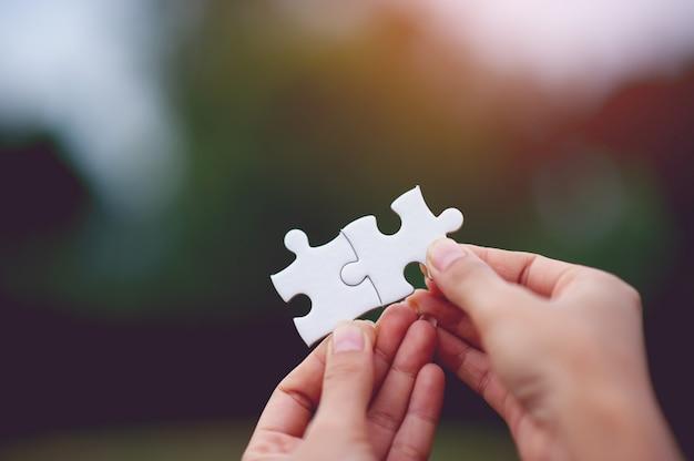 Hände, die stücke eines puzzlespiels halten