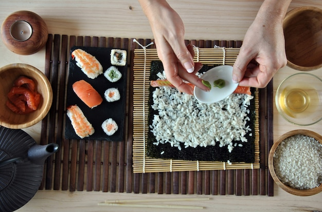 Hände, die sushi mit reis, lachsen und nori kochen