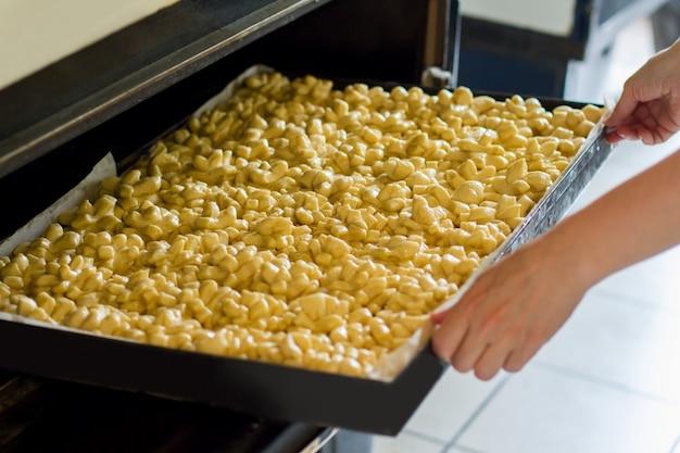 Hände, die tablett mit teig halten viele rohe teigstücke. baker bereitet leckere brötchen zu. arbeite in der bäckerei.