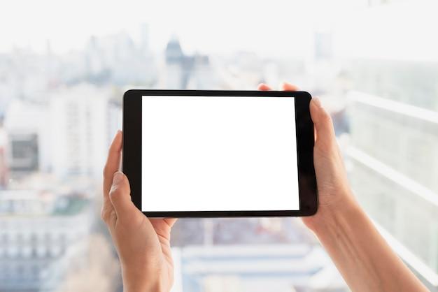 Hände, die tablette mit hellem hintergrund halten