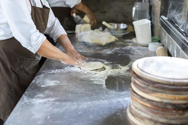 Hände, die teig für die pizzabildung kneten, chef, der unterseite für die herstellung des traditionellen italieners vorbereitet
