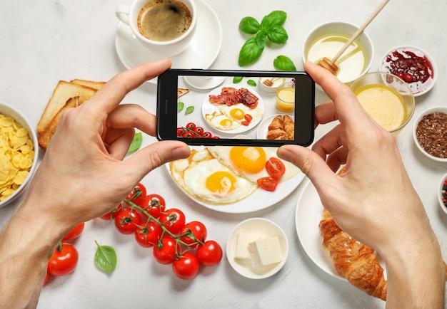 Hände, die telefon halten und ein foto von der frühstückswohnung machen.