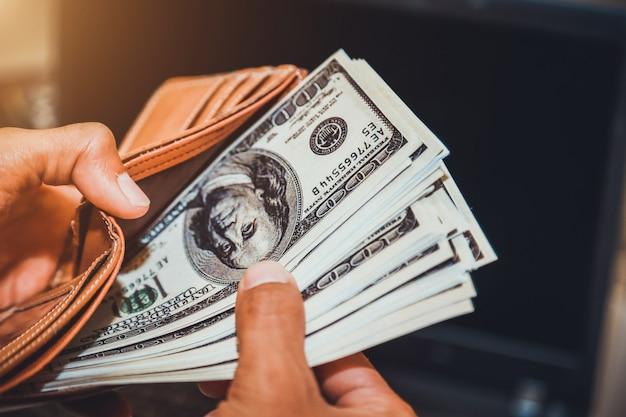 Hände, die uns dollarscheine und geldbeutel halten.