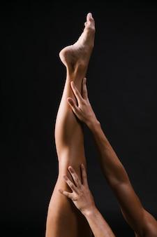 Hände, die verlängertes bein auf schwarzem hintergrund berühren