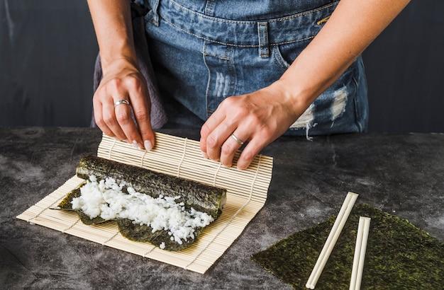 Hände, die verpackung mit sushimatte tun
