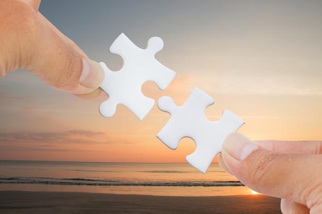 Hände, die versuchen, puzzlestück mit see- und strandhintergrund zu verbinden.