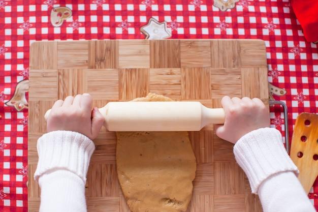 Hände, die vom teig weihnachtslebkuchenmann machen