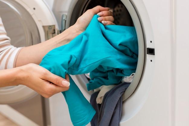 Hände, die waschmaschine der kleidung herausnehmen