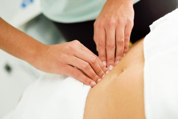 Hände, die weiblichen unterleib massieren therapeut, der druck auf bauch anwendet.
