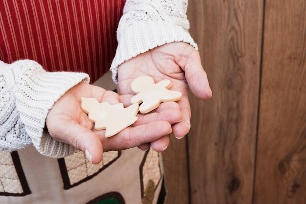 Hände, die weihnachtsbaum und mann halten, formten gebäck