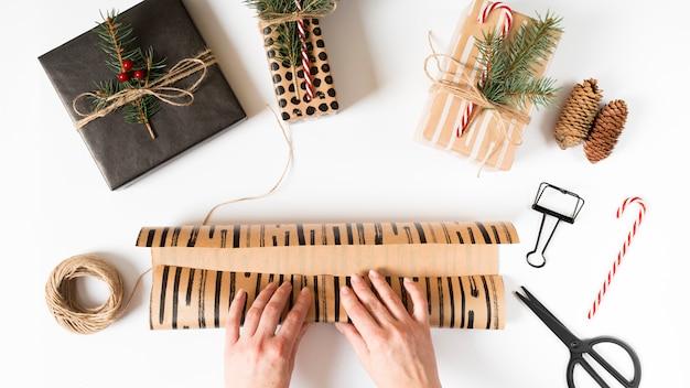Hände, die weihnachtsgeschenk im verpackungspapier einwickeln