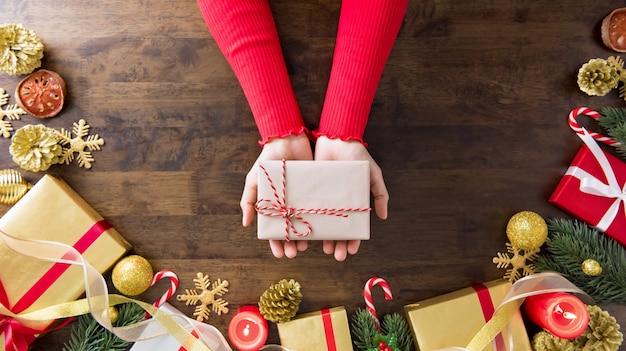 Hände, die weihnachtsgeschenkbox auf hölzerner tabelle zeigen