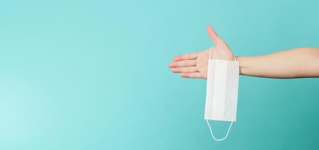 Hände, die weiße chirurgische gesichtsmaske halten. medizinische maske auf blauem und grünem oder tiffany blue-hintergrund.