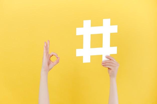 Hände, die weißes hashtag-zeichen halten und eine okaygeste zeigen showing