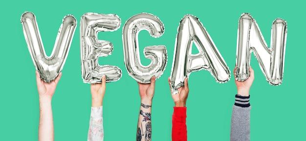 Hände, die wort des strengen vegetariers in den ballonbuchstaben halten