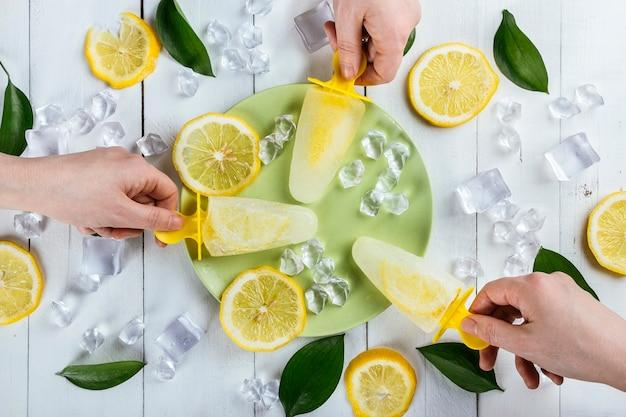 Hände, die zitroneneis am stiel von einem teller auf einem weißen holztisch aufheben, der mit eiswürfeln, zitronenscheiben und naturblättern bedeckt ist